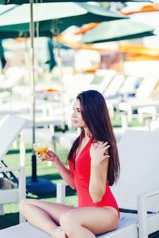 Donna castana con un bicchiere di succo