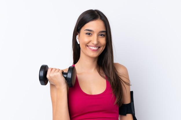Donna castana di giovane sport sopra la parete bianca isolata che fa sollevamento pesi
