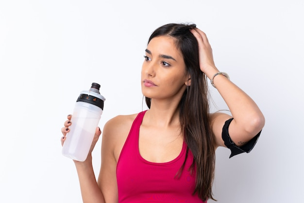 Donna castana di sport giovane sopra la parete bianca isolata con la bottiglia di acqua di sport