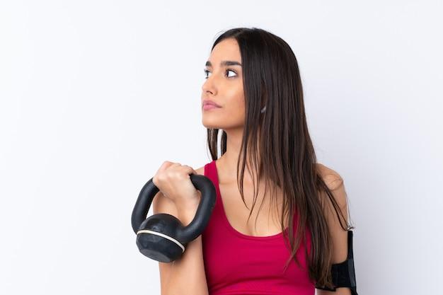 Donna castana di sport giovane sopra sollevamento pesi di fabbricazione bianco con kettlebell