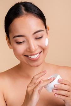 Donna castana felice del primo piano con crema per il viso