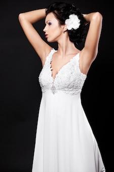 Donna castana felice felice della bella sposa in vestito da sposa bianco e trucco luminoso