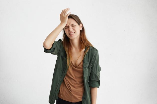 Donna castana frustrata che indossa abiti casual tenendo la mano sulla fronte essendo depressa rimpiangendo quello che ha fatto avendo mal di testa. donna confusa con la fronte accigliata che sembra stressante avendo un po 'di dolore