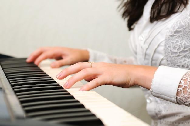 Donna castana in camicetta bianca che gioca il pianoforte