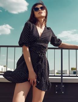 Donna castana intelligente splendida in vestito da modo che posa sul tetto di una costruzione