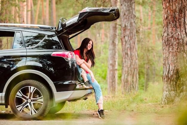 Donna castana nella foto a figura intera dell'automobile