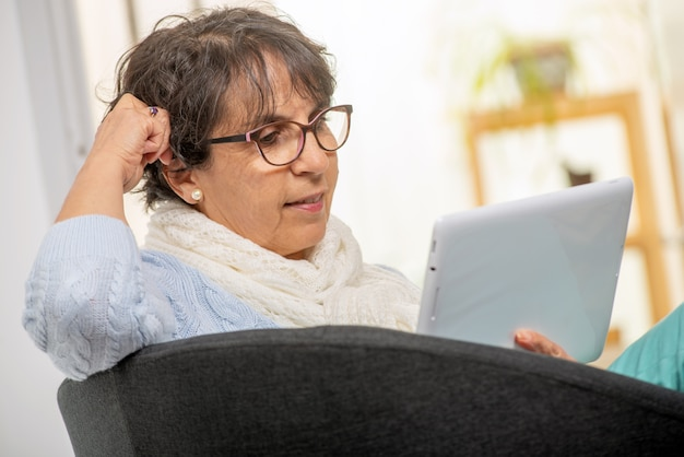 Donna castana senior affascinante con i vetri facendo uso della compressa digitale a casa