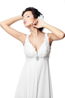 Donna castana sexy felice della bella sposa in vestito da sposa bianco con l'acconciatura e trucco luminoso con il fiore in capelli isolati su bianco