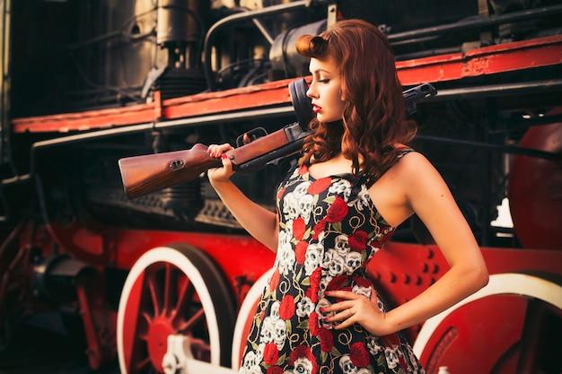 Donna castana sexy in stile pin up retrò vicino al vecchio treno. tiene il fucile