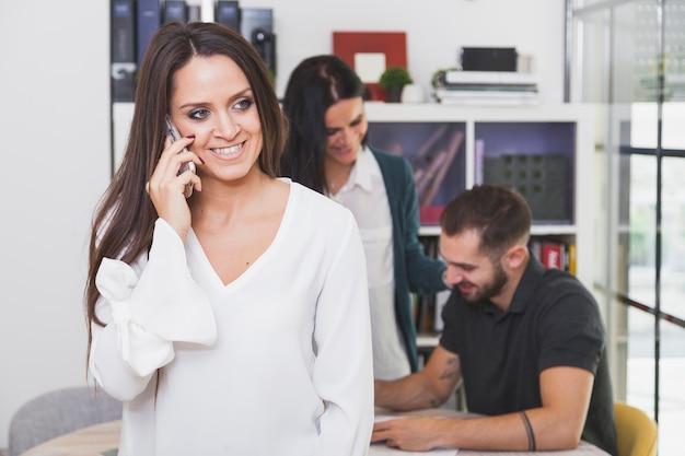 Donna castana sorridente che parla sul telefono