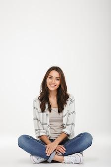 Donna castana sorridente verticale in camicia che si siede sul pavimento e che esamina la macchina fotografica sopra grey