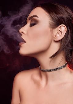 Donna castana splendida seducente di fascino che fuma sigaretta elettronica