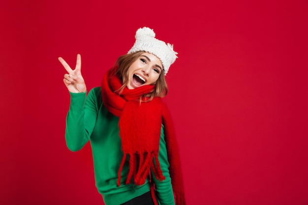 Donna castana urlando allegra in maglione, cappello divertente e sciarpa