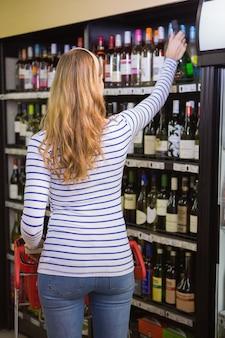 Donna casuale che cattura bottiglia di vino