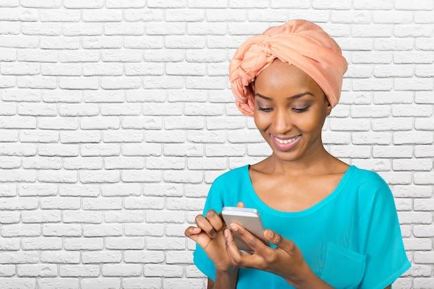 Donna casuale che manda un sms sul telefono