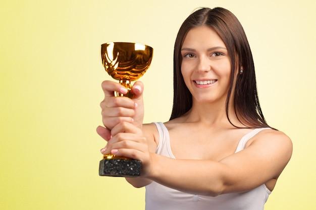 Donna casuale felice che mostra il suo grande trofeo