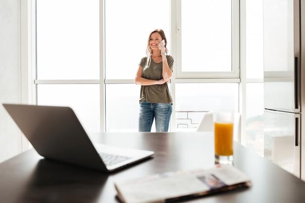 Donna casuale felice che parla sullo smartphone vicino alla finestra