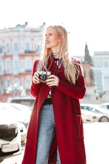 Donna caucasica abbastanza giovane che cammina all'aperto che tiene macchina fotografica