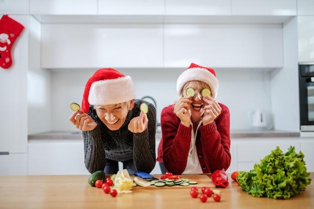 Donna caucasica allegra che tiene le fette del cetriolo davanti ai suoi occhi mentre appoggiandosi sul bancone della cucina. sua madre le sta accanto e ride. entrambi hanno cappelli di babbo natale in testa.