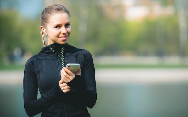 Donna caucasica attraente che utilizza il suo telefono, cuffia senza fili mentre correndo nel parco