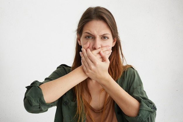 Donna caucasica che copre la bocca con le mani cercando di mantenere il silenzio e di non dire il segreto della sua famiglia. giovane femmina con gesti di aspetto grazioso