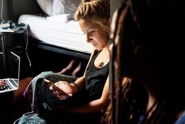 Donna caucasica che si siede sul pavimento per mezzo del telefono mobile