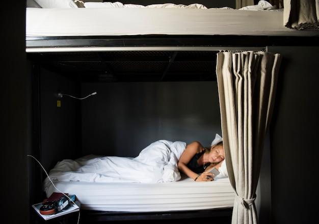 Donna caucasica che si trova sul letto facendo uso del telefono cellulare