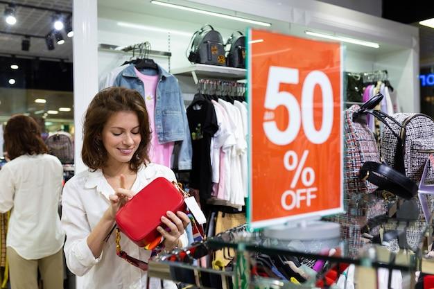 Donna caucasica che tiene la borsa rossa luminosa della borsa in sua mano con il bello sorriso. segno di stagione di vendita.