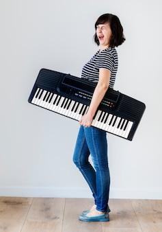 Donna caucasica che tiene una tastiera elettronica