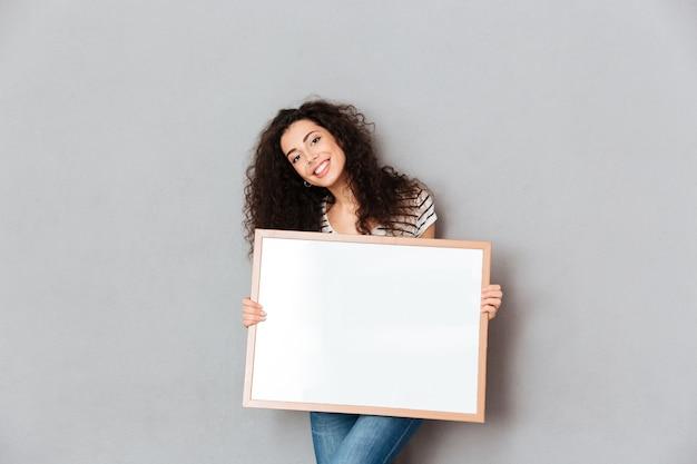 Donna caucasica con bei capelli che posano sopra la parete grigia che tiene opera d'arte in mani che esprimono ammirazione per lo spazio della copia del ritratto