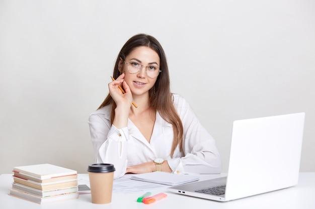 Donna caucasica con i capelli lunghi, indossa gli occhiali, guarda il webinar sul computer portatile, prepara il progetto, fa i compiti, beve il caffè da asporto, isolato su bianco