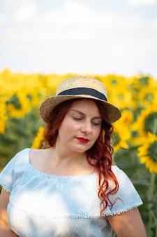 Donna caucasica dei giovani capelli rossi in vestito dal cotone di estate e cappello di paglia in un campo dei girasoli gialli un giorno soleggiato.