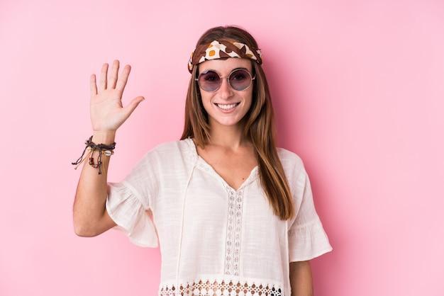 Donna caucasica dei giovani pantaloni a vita bassa che sorride mostrando numero cinque di mostra allegro con le dita.