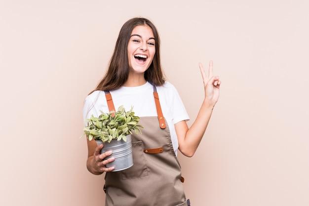 Donna caucasica del giovane giardiniere che tiene una pianta allegra e spensierata che mostra un simbolo di pace con le dita.