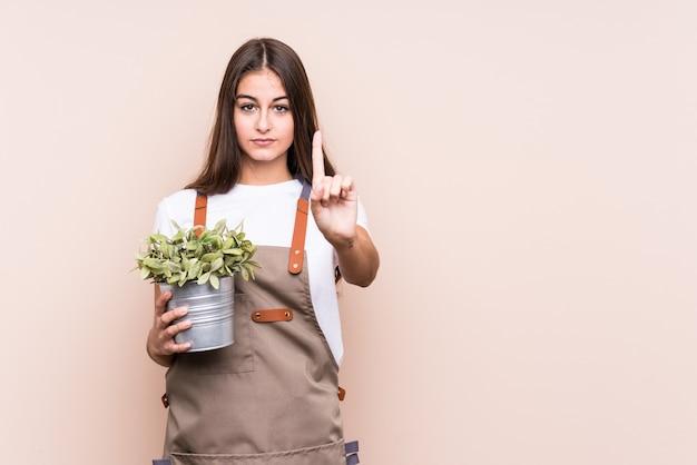 Donna caucasica del giovane giardiniere che tiene una pianta numero uno isolatedshowing con il dito.