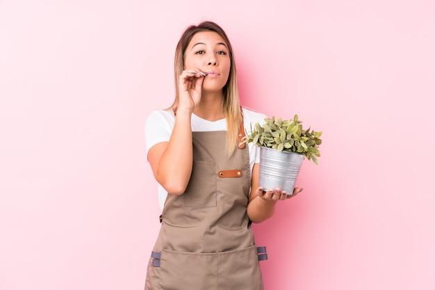 Donna caucasica del giovane giardiniere isolata con le dita sulle labbra che tengono un segreto.