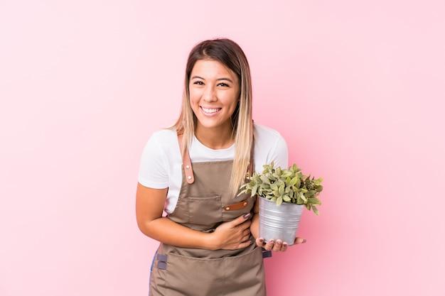 Donna caucasica del giovane giardiniere isolata ridendo e divertendosi.