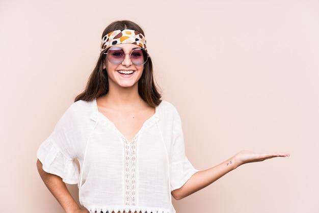 Donna caucasica del giovane hipter che mostra uno spazio in bianco su una palma e che tiene un'altra mano sulla vita.