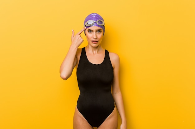 Donna caucasica del giovane nuotatore che mostra un gesto di delusione con l'indice.
