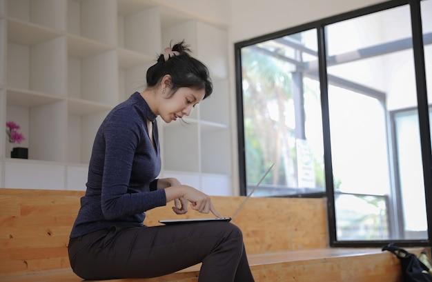 Donna caucasica di affari che si siede e che scrive sul computer portatile