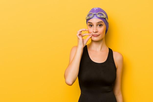 Donna caucasica giovane nuotatore con le dita sulle labbra mantenendo un segreto.