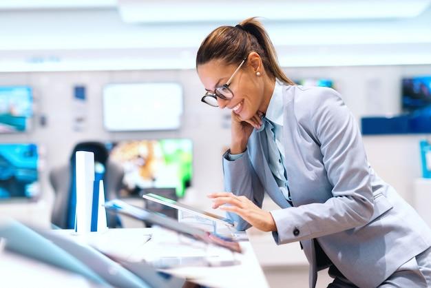 Donna caucasica in abbigliamento formale provando nuovo dispositivo tablet. interno del negozio di tecnologia.