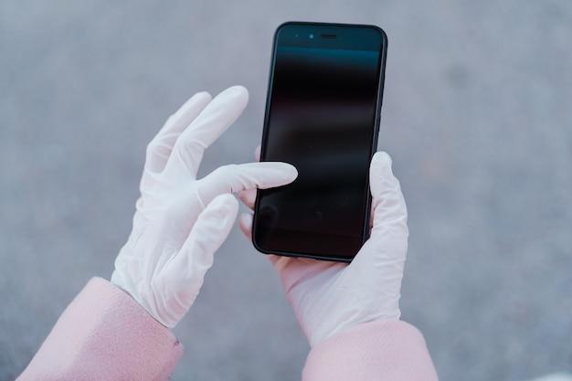 Donna caucasica in strada indossando guanti protettivi e utilizzando il telefono cellulare