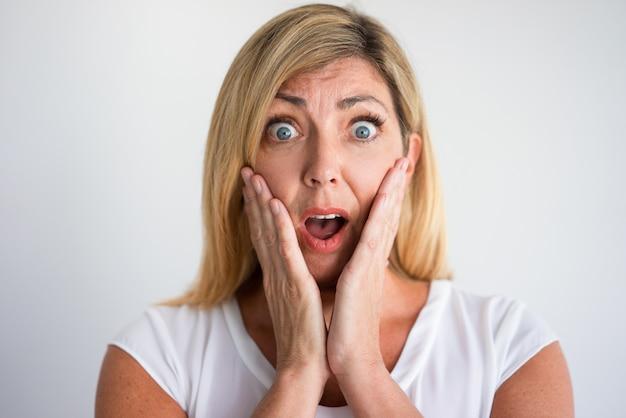 Donna caucasica matura scioccata con le guance della copertura della bocca aperta con le mani