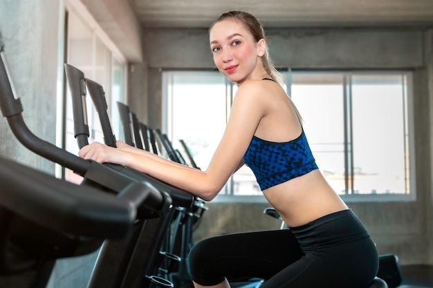 Donna caucasica perfetta in cardio di addestramento di ciclismo degli abiti sportivi alla palestra di forma fisica.