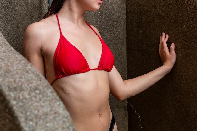 Donna caucasica sexy in bikini rosso che inonda all'esterno.