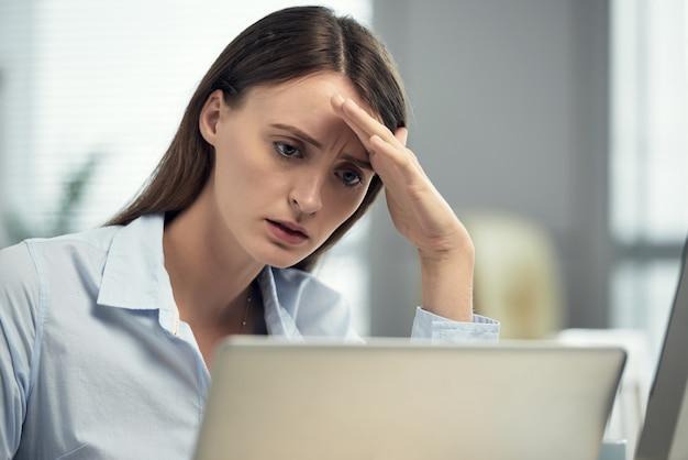 Donna caucasica sollecitata che si siede nell'ufficio davanti al computer portatile