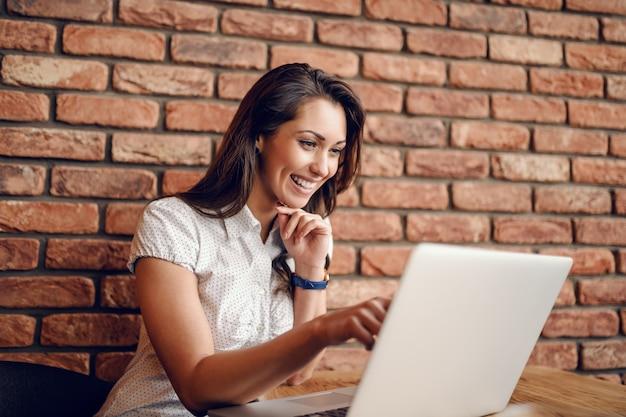 Donna caucasica sveglia sorridente che indica al computer portatile e che tiene mano sul mento mentre sedendosi nel caffè. sullo sfondo di un muro di mattoni.