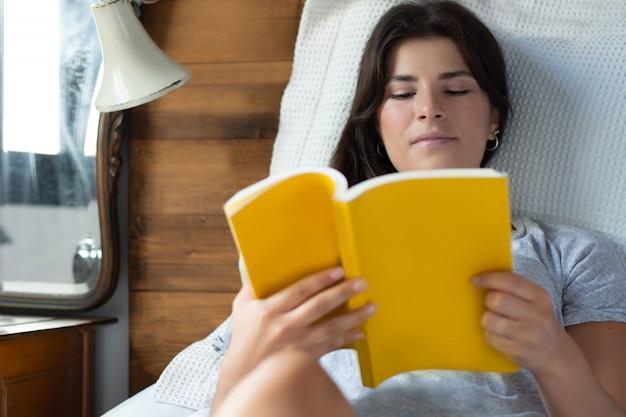 Donna che a letto e leggendo il libro