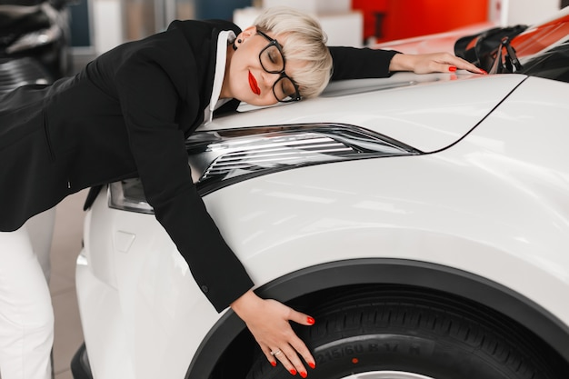 Donna che abbraccia automobile bianca con grande piacere e chiuse gli occhi.